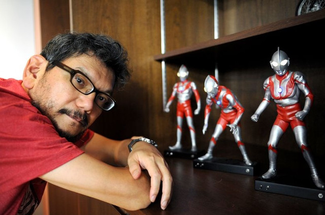 Director Hideaki Anno poses next to a display of figures of various Ultraman heroes.