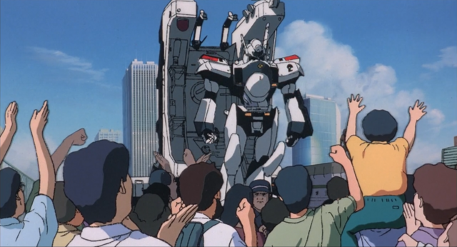 Civilians cheer as the AV-98 Ingram Patlabor is pneumatically lifted into action.