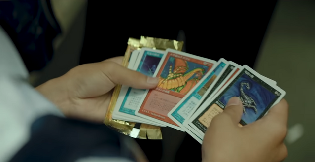 A young Japanese student cracks a pack of Magic: The Gathering cards, obtaining a Shivan Dragon in the process.