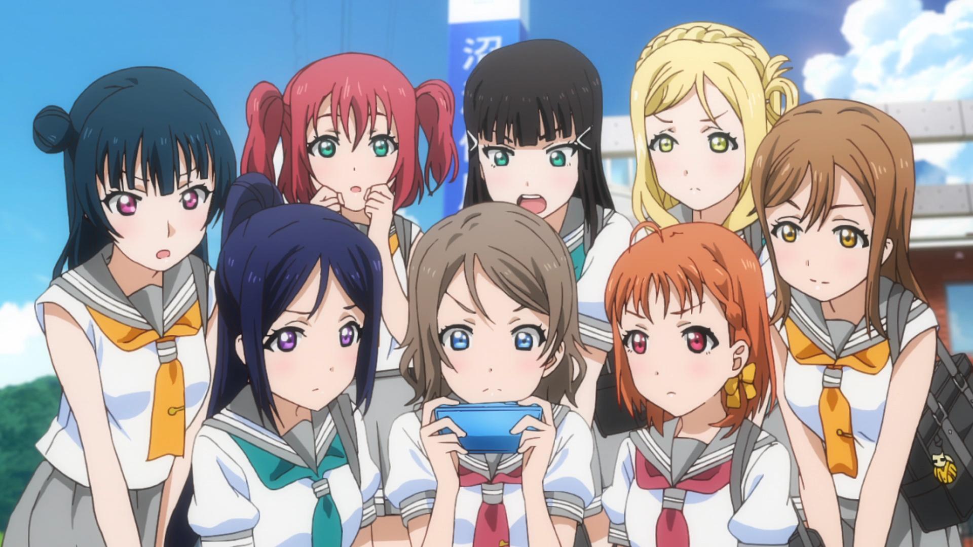 ¡Las chicas de Aqours se reúnen alrededor de un teléfono inteligente para ver las clasificaciones de ídolos de la escuela en una escena de Love Live!  ¡¡Brillo Solar!!  Anime de TV.