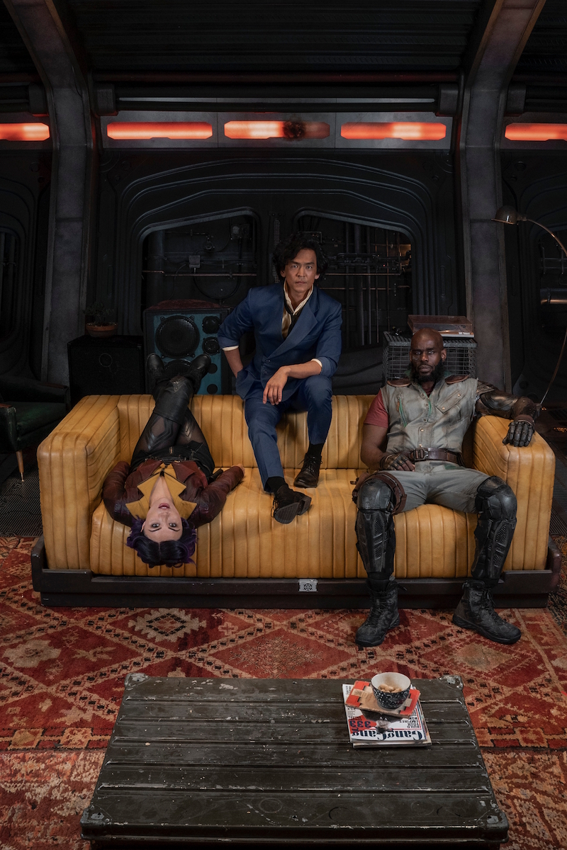 A promotional poster for Netflix's upcoming live-action Cowboy Bebop series, featuring the main cast in full costume and make-up hanging out on a couch in the hull of the Bebop space trawler.