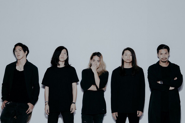 The five members of Survive Said the Prophet stand in a line against a white backdrop.