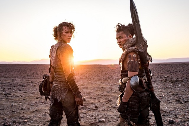Actors Milla Jovovich and Tony Jaa pose for a promotional photo in full costume and make-up from the set of the 2020 live-action Monster Hunter film, directed by Paul W.S. Anderson.