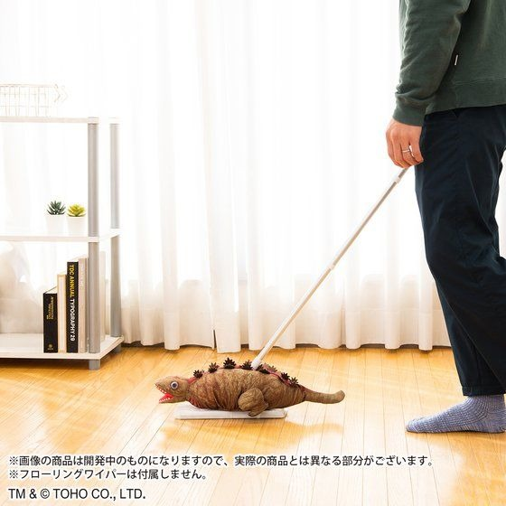 A promotional image of the Shin Godzilla 2nd Form Flooring Wiper Cover character good, depicting the product being used along with a flooring wiper to clean a Japanese style apartment floor.