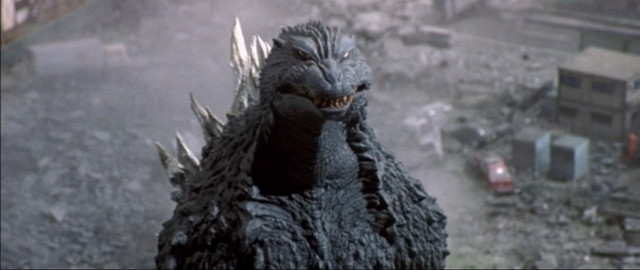 Godzilla stares at its off-screen opponent with a quizzical expression on its face.