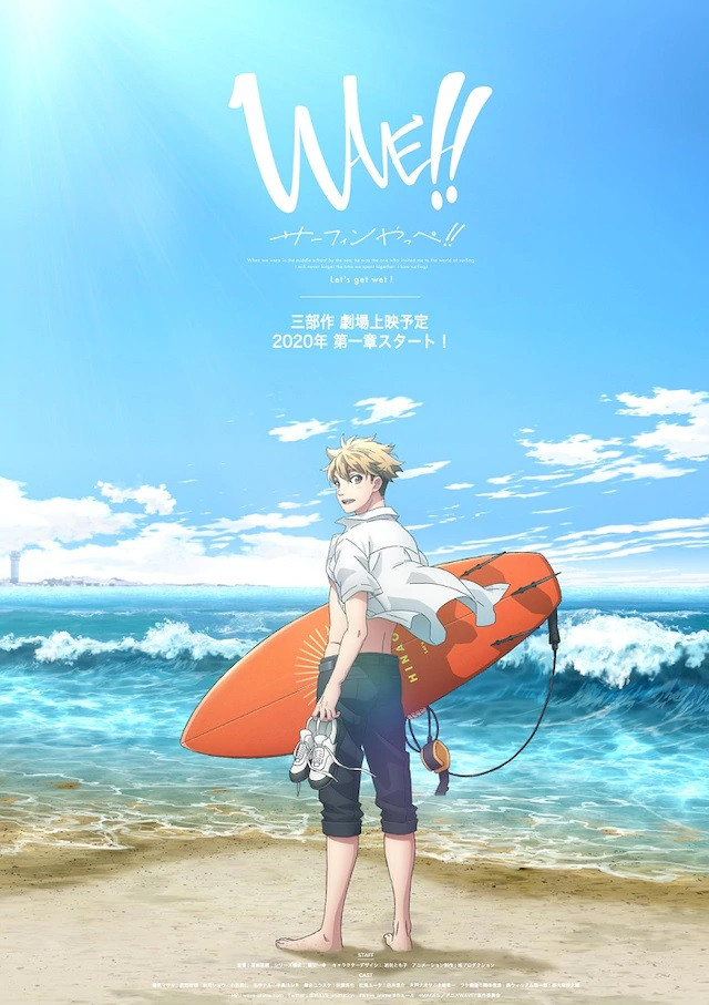 A key visual for the upcoming WAVE!! anime theatrical film, featuring the main character, Masaki Hinaoka, standing at the edge of a lapping surf with his shoes in one hand and his surfboard in the other.
