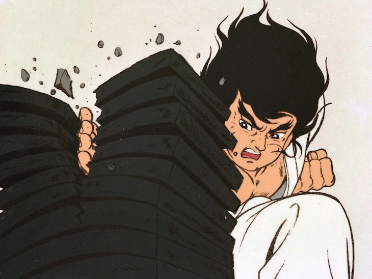 Ichidai breaks a stack of ceramic roof tiles with a powerful karate chop in a promotional image for the 1973 - 1974 Karate Master TV anime.