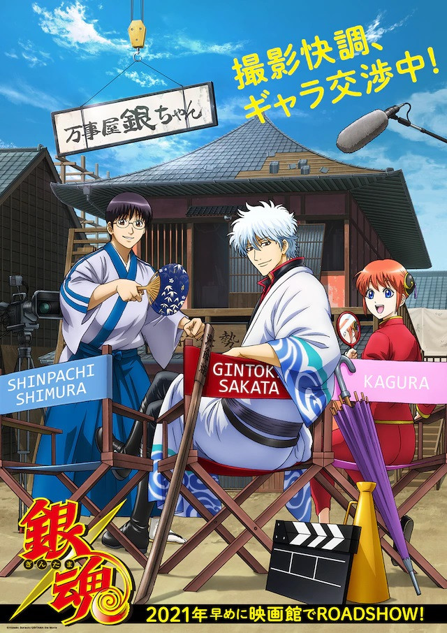 """A """"super teaser visual"""" for the newly announced Gintama theatrical anime film, featuring Shinpachi, Gintoki, and Kagura hanging out in director's chairs on the movie set of the Yorozuya Gin-chan building."""
