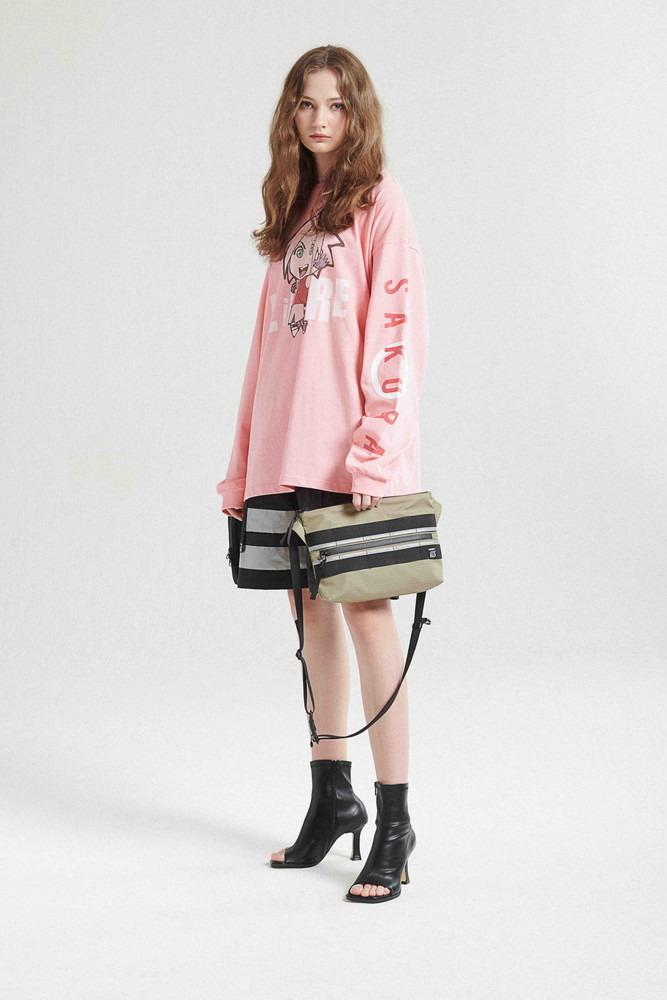 Una joven modela el SAKURA LONGSLEEVE / PINK y el TERRAIN CROSS BAG / KHAKI de la colaboración de moda callejera LIBERE FOR NARUTO.