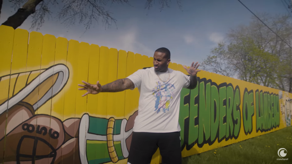 Professional football player Mike Daniels strikes a pose in front of a piece of street art depicting a Black Saiyan from Dragon Ball Z in a scene from the He Was Anime Youtube documentary.