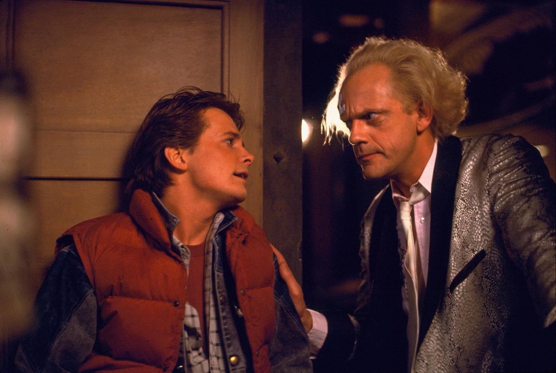 Los actores Michael J. Fox y Christopher Llyod interactúan interpretando a sus personajes Marty McFly y Doc Brown en una escena de la película de 1985, Regreso al futuro.