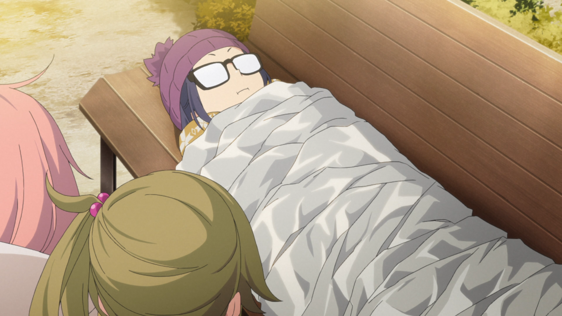 Chiaki Ogaki, Nadeshiko Kagamihara, and Aoi Inuyama of the Outdoor Activities Club attempt to turn a thin summer camping blanket into an insulated winter camping blanket with a copious application of bubble-wrap, aluminum foil, and cardboard in a scene from the 2018 Laid-Back Camp TV anime.