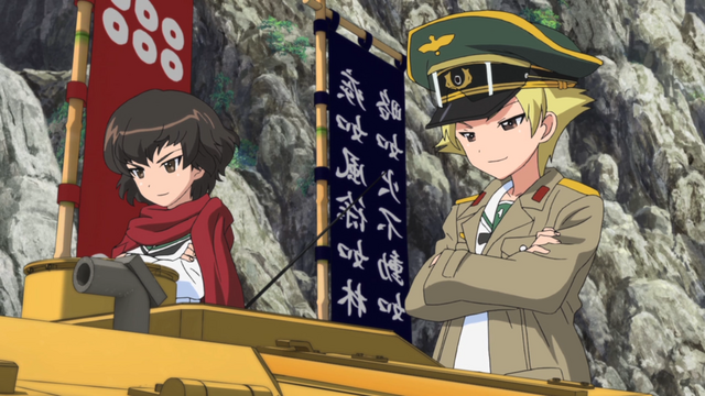 Caesar and Erwin of Hippo Team flaunt their tank's flashy paint job and banners in a scene from the 2012 GIRLS und PANZER TV anime.