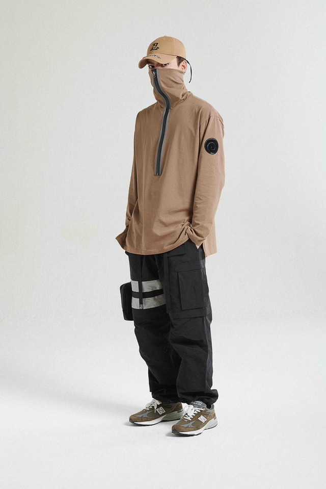 Un joven modela la CAMISETA NINJA NECK SHIRT / KHAKI, el 2-1 TACTICAL PANTS / BLACK y la 6 PANEL UNION CAP / KHAKI de la colaboración de moda callejera LIBERE FOR NARUTO.