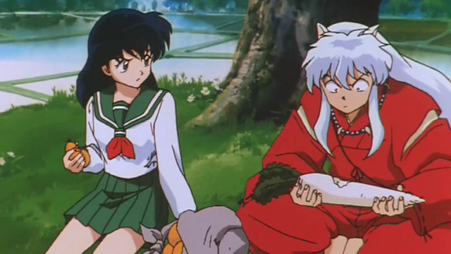 Kagome and Inuyasha share a snack in a scene from the Inuyasha TV anime.