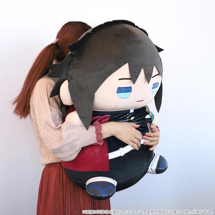Una modelo abraza un peluche extra grande de Mame Mate Giyu Tomioka en una imagen promocional.
