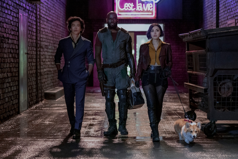 A promotional image for Netflix's upcoming Cowboy Bebop live-action series, featuring the main cast of John Cho, Musafa Shakir, and Daniella Pineda in full costume and make-up as Spike Spiegel, Jet Black, and Faye Valentine, respectively. The three bounty hunters stride down a darkened alley while walking with Ein, a super intelligent Welshi corgi dog, on a leash.