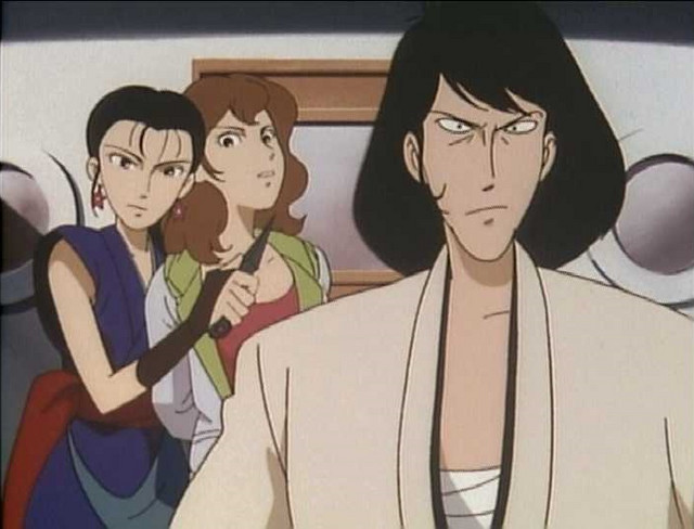 A screen capture from the 1994 Lupin the Third: Dragon of Doom TV special, featuring Kikyo holding a kunai to Fujiko Mine's throat in the background while Goemon sports a stern expression in the foreground.