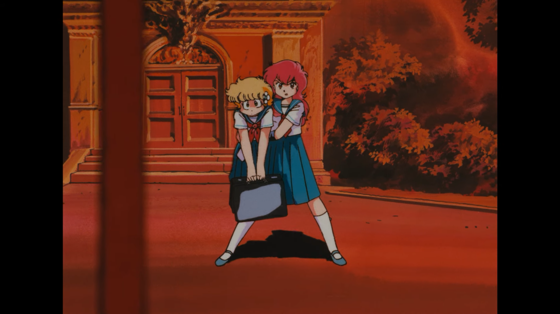 While carrying her best friend C-ko Kotobuki like a stuffed animal, perfectly ordinary Japanese high school girl scolds B-ko Daitokuji for ambushing her (again) with an arsenal of giant robots on the way to school in a scene from the 1986 Project A-ko theatrical anime film.