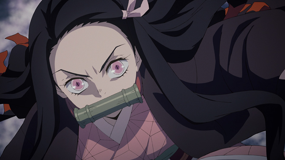 Nezuko Kamado, still wearing her bamboo gag, prepares to fight to protect her younger brother, Tanjiro, in a scene from the Demon Slayer: Kimetsu no Yaiba TV anime.