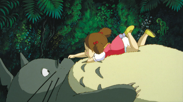 Mei and Totoro cuddle in the forest in a screen capture from the 1988 anime theatrical film, My Neighbor Totoro.
