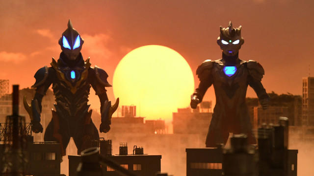 Ultraman Zero and Ultraman Z prepare to protect the Earth as the sun sinks low on the horizon behind them in a scene from the upcoming Ultraman Z TV series.