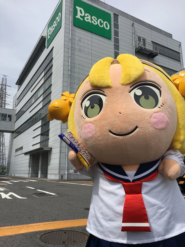 The Big Yatogame-chan mascot character poses with a sandwich roll outside of the Pasco building in Nagoya City, Aichi Prefecture.