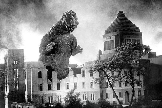 A promotional image from the original 1954 Gojira film, directed by Ishiro Honda, featuring the iconic movie monster attacking the National Diet Building.