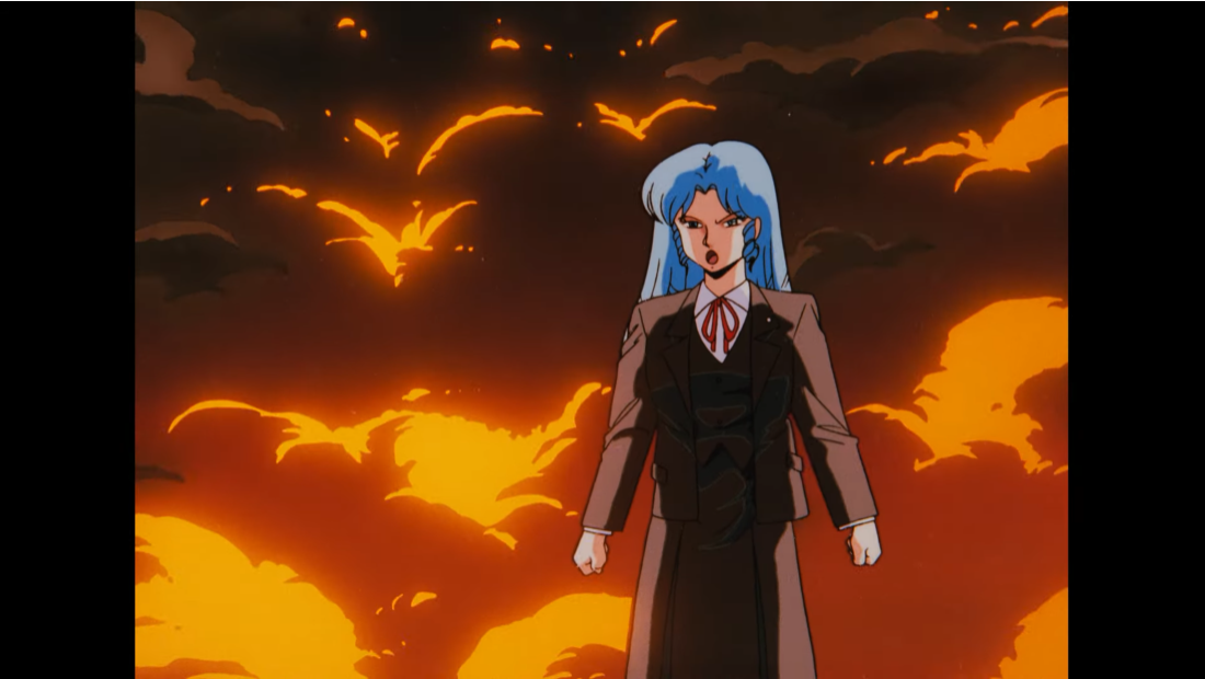 C-ko Daitokuji poses dramatically in front of the smoke and billowing flames of her failed robot creations in a scene from the 1986 Project A-ko theatrical anime film.