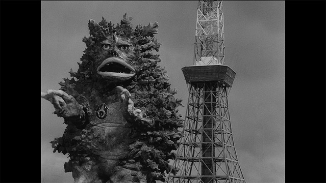 """A screen capture from the 4K restoration of the """"Garamon Strikes Back"""" episode of the 1966 Ultra Q tokusatsu TV series, featuring the titular monster attacking Tokyo Tower."""