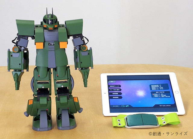"A promotional photo of the miniature Zaku toy, a tablet computer running the ZEONIC TECHNICS smart phone software, and the XB-01 sensor for the ""ZEONIC TECHNICS Robotics and Programming Course I"" experiment."