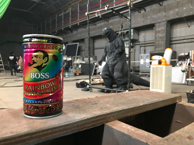 Behind the scenes at the Boss Coffee x Godzilla collaboration, a can of Boss Coffee takes the lead while the Godzilla suit lingers in the background.