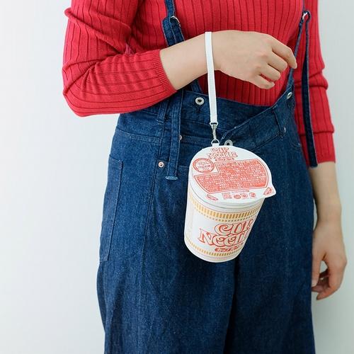 Un modelo demuestra cómo llevar la bolsa de Cup Noodle de gran tamaño incluida como paquete de edición limitada como bono con el CUP NOODLE 50TH ANNIVERSARY BOOK de Takarajimasha.