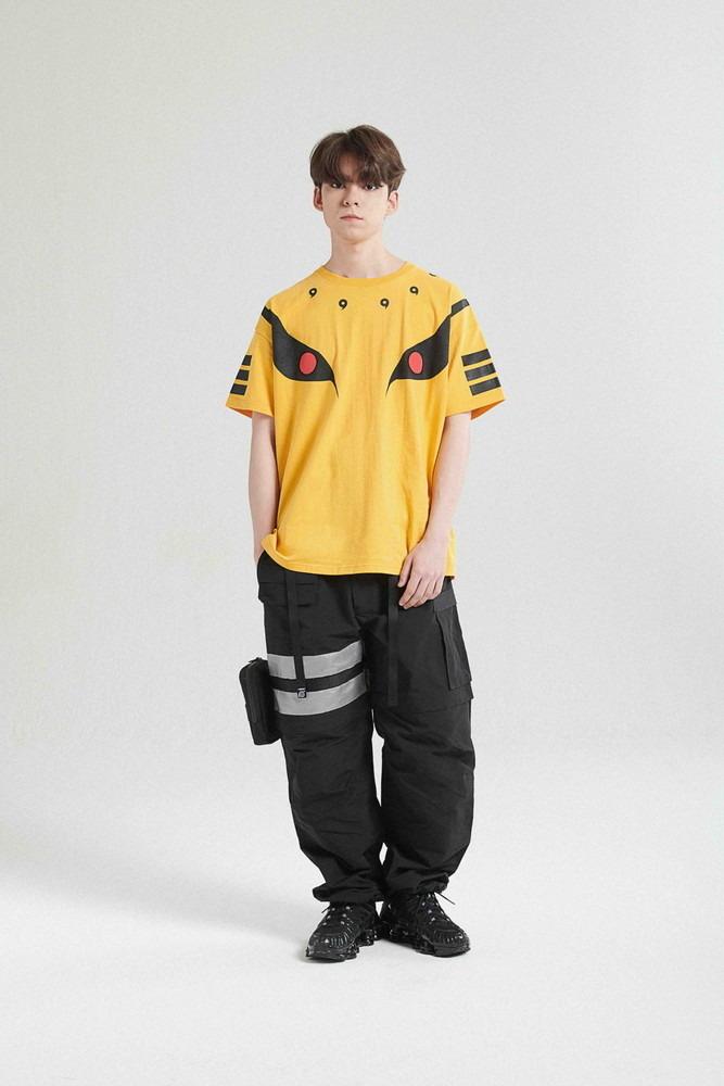 Un joven modela la camiseta KURAMA y el 2-1 TACTICAL PANTS / BLACK de la colaboración de moda callejera LIBERE FOR NARUTO.
