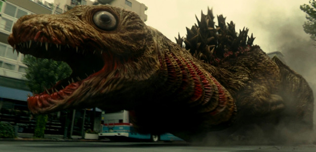 A googly-eyed immature form of Godzilla takes a leisurely waddle through Kamata, leaving destruction in its wake.