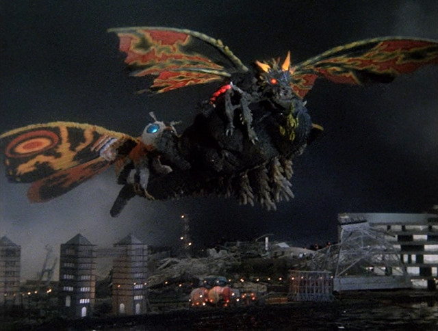Mothra and Battra prepare to yeet a stunned Godzilla into the Pacific Ocean.