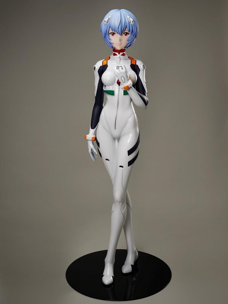 Una imagen promocional de la figura a escala 1: 1 de Rei Ayanami de F: NEX, con una toma amplia de un prototipo de la figura que muestra su tamaño completo, así como el pedestal de exhibición.