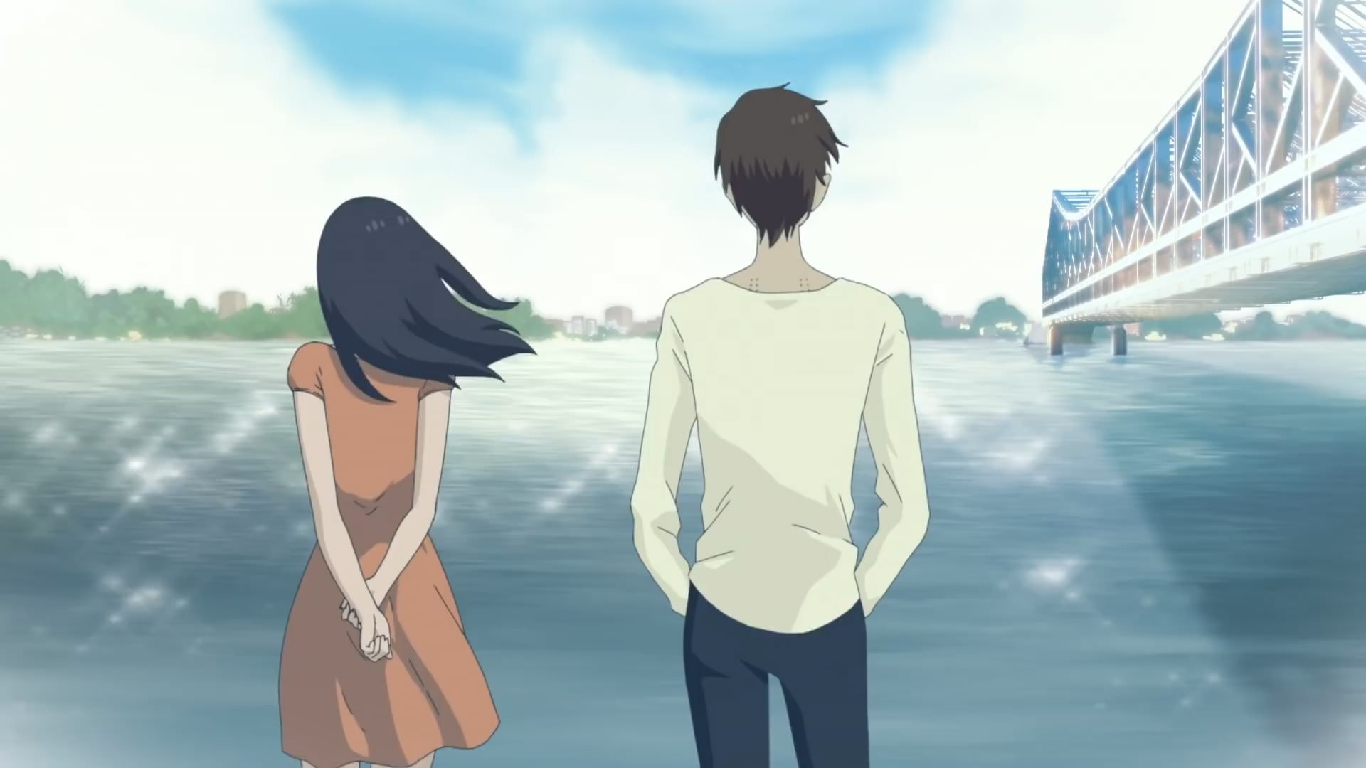 A woman and a man stand by the water near a bridge