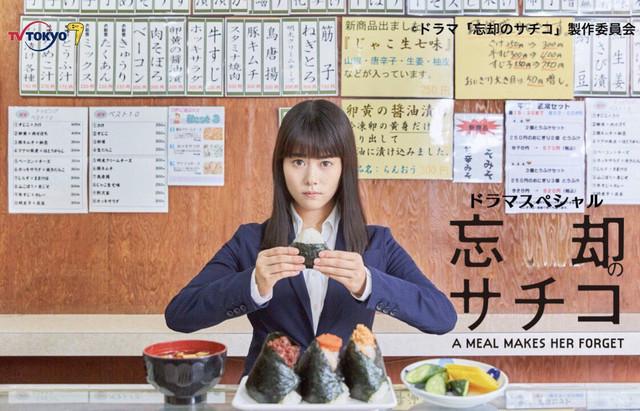 ميتسُكي تاكاهاتا مجسدة دور ساتشيكو ساساكي. تجلس في مطعم ما وممسكة بكرة رز وعلى الطولة كرات رز أخرى