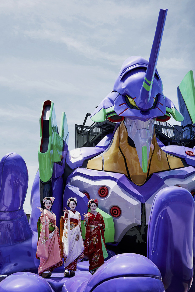 Three actresses dressed as geisha pose in the palm of Eva Unit-01's hand at the Evangelion Kyoto Base attraction at Toei Kyoto Studio Park.