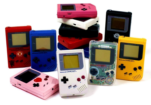An image of a collection of Nintendo Game Boy handheld video game consoles, including the original gray model and several of its more colorful versions.