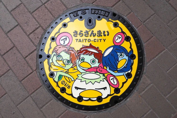A promotional photo of the custom manhole cover, decorated with the cast of the Sarazanmai TV anime, that was installed on April 13, 2021, near the Kappabashi intersection in Taito City, Tokyo, Japan.