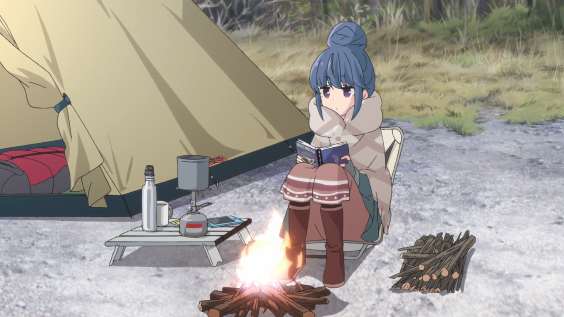 Surrounded by her tent and modern camping gear, Rin Shima enjoys some solo camping by reading a book near a campfire during a cold winter day in a scene from the 2018 Laid-Back Camp TV anime.