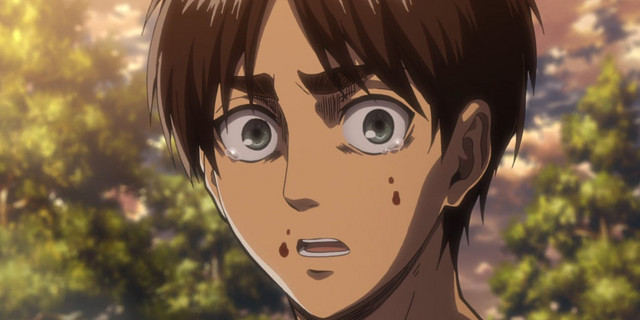 A close-up of Eren Jaeger's distraught face in a scene from the Attack on Titan TV anime.