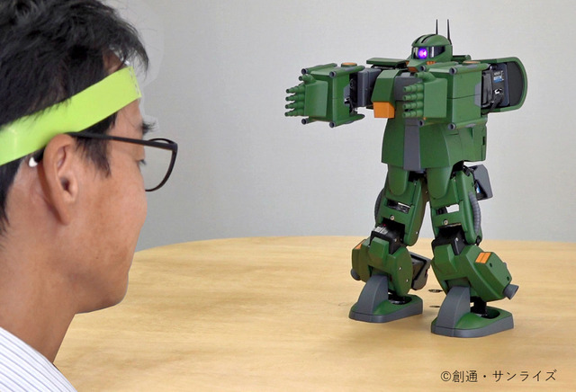 A researcher dons a XB-01 cerebral bloodflow sensor and operates a motorized, remote control Zaku toy by issuing it mental commands interpreted by a smart phone app as part of the ZEONIC TECHNICS Robotics and Programming Course I.