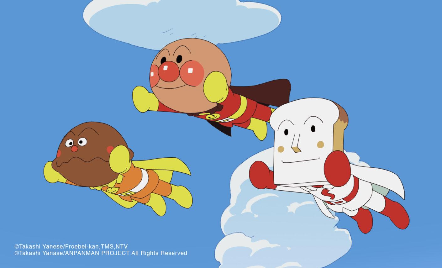Una imagen promocional para la serie de anime de Anpanman, con el personaje principal y dos de sus amigos con cabeza de pan volando por el cielo con sus trajes de superhéroe.