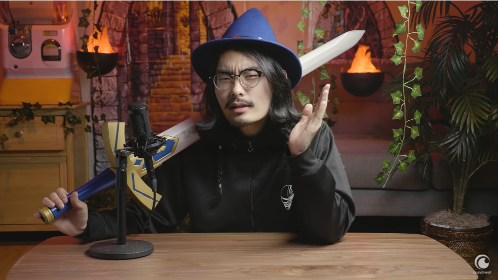 Tim Lyu dons a wizard had and brandishes the Master Sword from the Legend of Zelda video game series as he explains the history of isekai anime in front of a backdrop designed to look like a fantasy dungeon in a scene from the Anime Explained Youtube video essay series.
