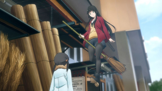 Makoto Kowata surprises her young cousin Chinatsu by tentatively levitating on a broom while shopping for housewares in a scene from the Flying Witch TV anime.